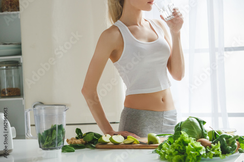 Cuadros en Lienzo Young woman making detox smoothie at home
