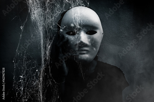 Mysterious woman in black wearing white mask hidden behind spider web,Scary back Wallpaper Mural