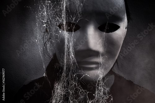 Photo  Mysterious woman in black wearing white mask hidden behind spider web,Scary back