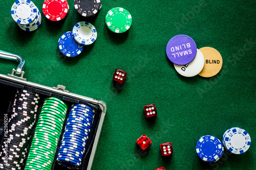 Poker set in a metallic case on a green gaming table top view плакат