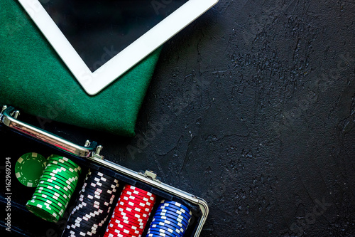 Poker set in a metallic case, green gambling cloth and tablet computer on a grey плакат
