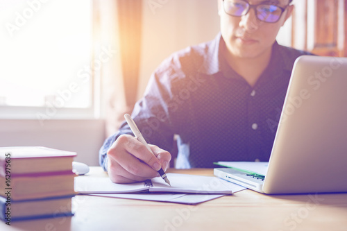 Young male student writes information from portable net-book while prepare for l Fototapet
