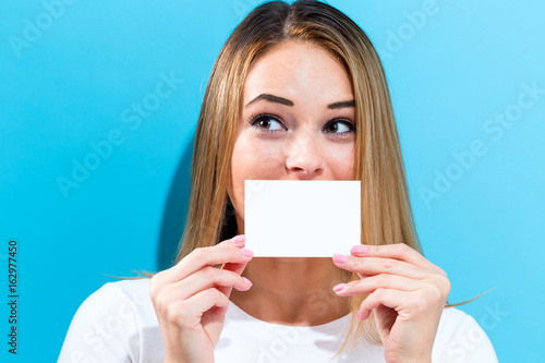 Fotografering  Woman holding a blank message card in front of her face