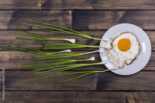 Deurstickers Gebakken Eieren Egg , chives and white plate look like sperm competition, Spermatozoons floating to ovule in wooden background