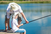 Dad Helps His Son Catch Fish With A Fishing Rod On The River