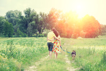 Happy Couple In Love With Dog Walking On A Rural Dirt Road In Springtime At Sunset. The Woman And Man Hugging. The Woman Keeps Her Dog On A Leash. Couple And Dog Back To The Camera. Casual Style.