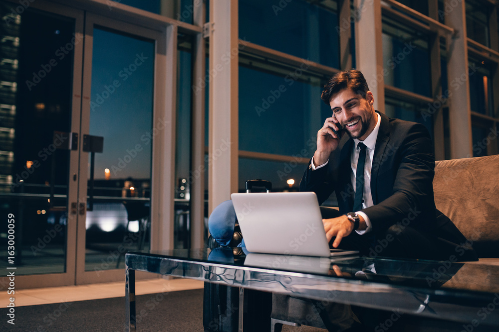 Fototapeta Smiling businessman with laptop talking on cellphone at the airp
