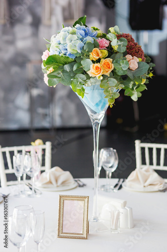 Table Set For Wedding Banquet With Floral Composition Of Roses And