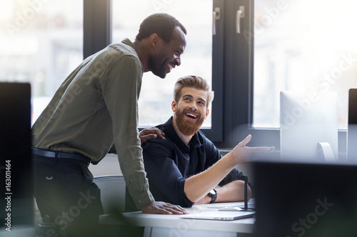 Two happy men working together on a new business project