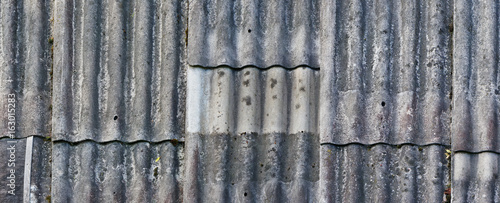 Photo Texture of an old vintage roof covered with wavy aged asbestos tiles