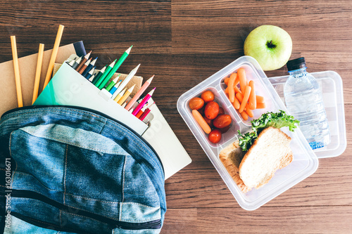 Fotografía  Lunch box with vegetables and slice of bread for a healthy school lunch on woode