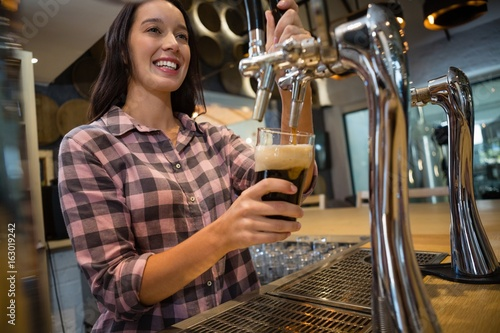 Beautiful barmaid preparing drink at bar Wallpaper Mural