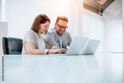 Group of confident business partners working with laptop in office