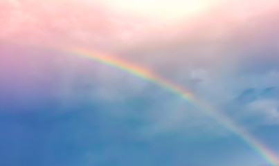 Blur and haze blue and pink pastel sky  with rainbow over the cloud after raining day with sunbeam