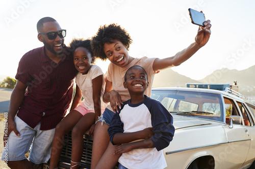 Obraz na plátne Family Posing For Selfie Next To Car Packed For Road Trip