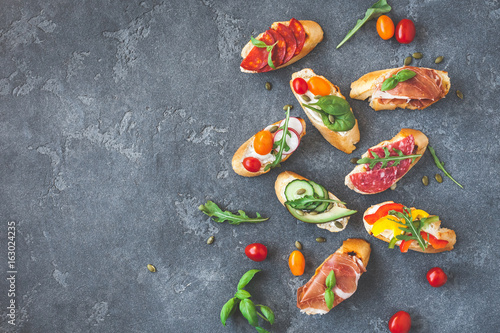 Traditional spanish tapas on black background. Flat lay, top view