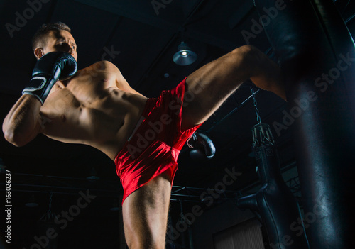 The fighter of mixed martial arts beats the bag with his left foot Fototapet