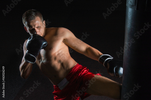 Photo  The fighter of mixed martial arts beats the bag with his left foot