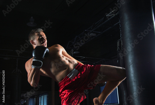 Fotobehang Vechtsport The fighter of mixed martial arts with a shout is hitting the bag
