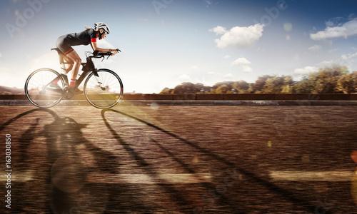 Zdjęcie XXL Sport. Rowerzysta jeździ na rowerze o zachodzie słońca. Dramatyczne tło.