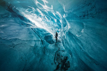 Guy With Crampons Exploring Gigantic Ice Cave In Iceland
