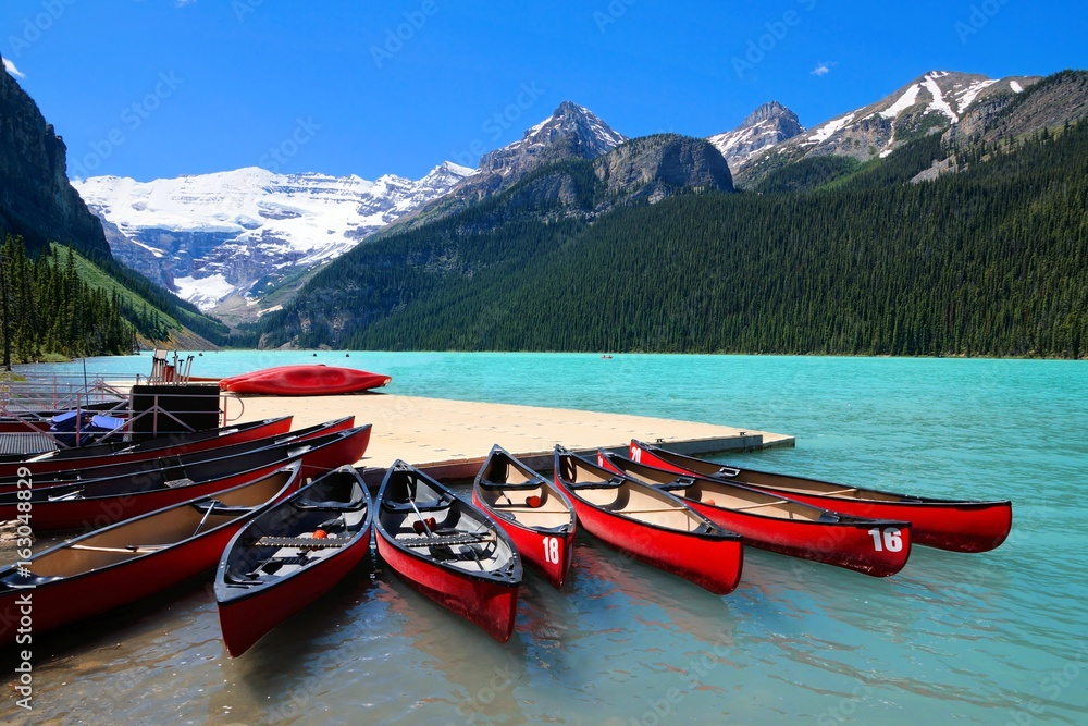 Fototapeta Red canoes in the blue waters of Lake Louise, Banff National Park, Alberta, Canada