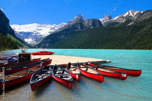 Fotobehang Canada Red canoes in the blue waters of Lake Louise, Banff National Park, Alberta, Canada