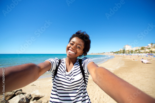 cheerful young afro american girl on the beach and talking selfie