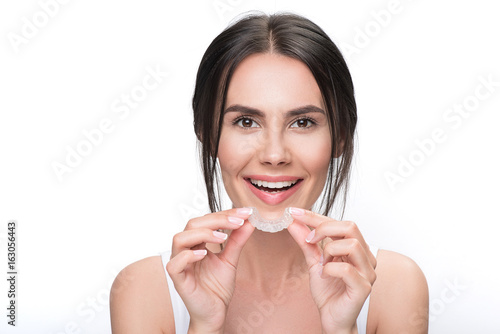 Fotografía  Excited young woman holding clear aligner