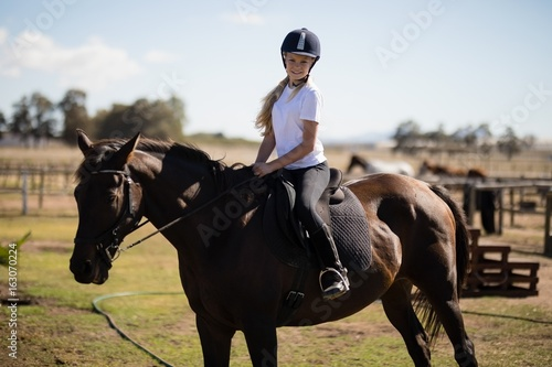 Poster Equitation Smiling girl riding a horse in the ranch