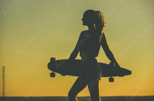 Fotografie, Obraz  Silhouette of a beautiful, sexy hipster girl in tattoos standing with a longboard against the sunset at the sea