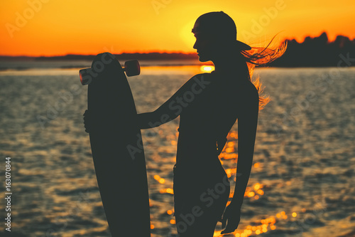 Fényképezés Silhouette of a beautiful, sexy hipster girl in tattoos standing with a longboard against the sunset at the sea