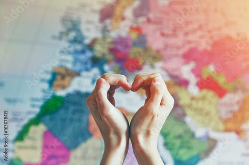 Plakat ręka w kształcie serca z miłością na tle mapy świata