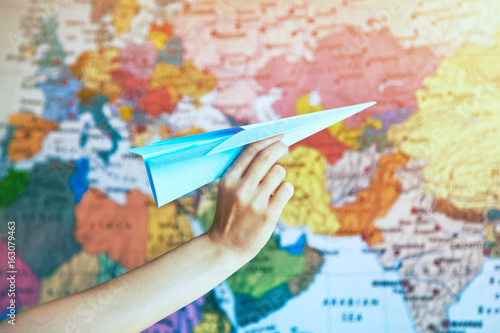 Foto op Canvas Wereldkaart hand with paper origami airplane on world map background