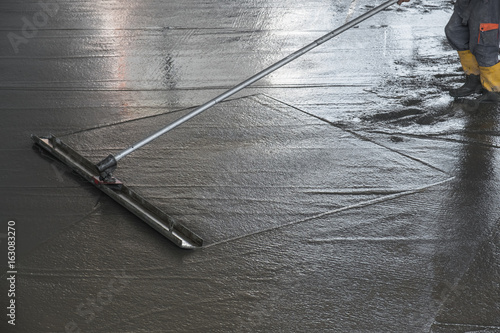 Fotografie, Obraz  Worker leveling fresh poured concrete floor with a channel float