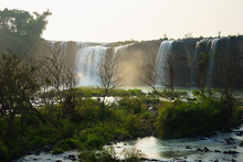 Waterfalls In The Morning With Dry Trees On Foreground
