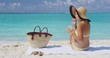 Vacation on beach. Woman sun tanning on summer tropical vacation drinking water wearing a cute retro stripes bikini, sunglasses, and hat outfit with straw bag and towel. RED EPIC SLOW MOTION.