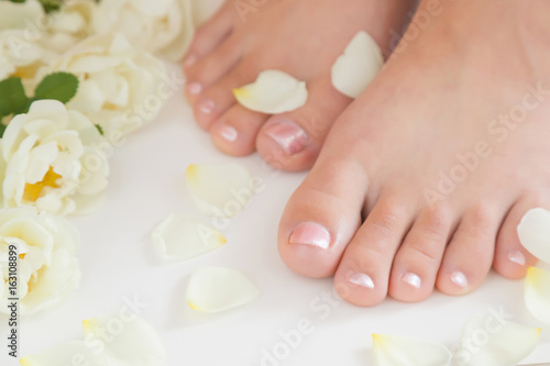 Poster Pedicure Young woman's feet. Smooth skin. Spring and summer atmosphere with fresh and fragrant white roses.