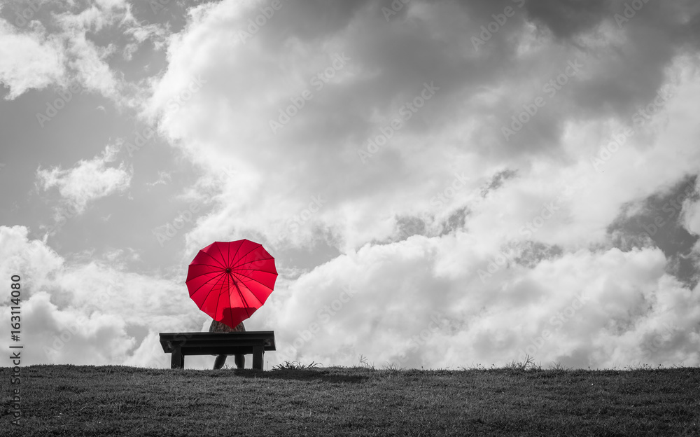 Fototapeta a women sitting alone on a bench with a red heart shaped umbrella waiting for love