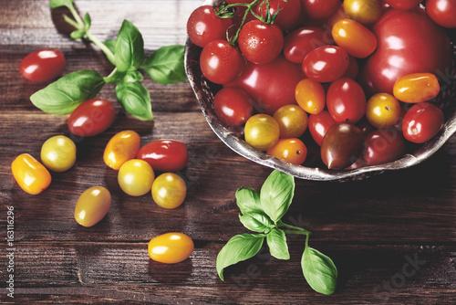 male-wloskie-pomidory-w-misce-i-liscie-bazylii