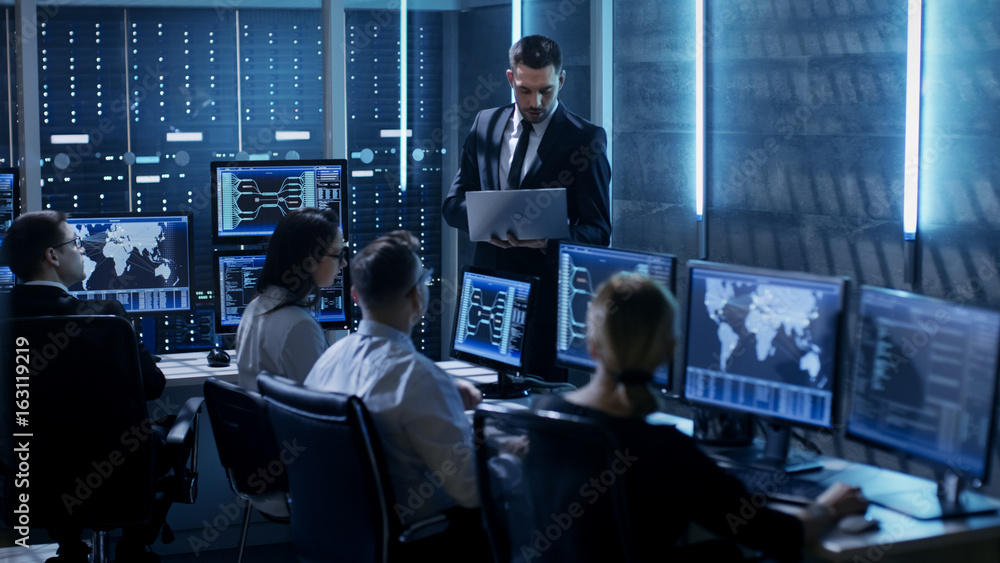 Fototapeta Professional IT Engineers Working in System Control Center Full of Monitors and Servers. Supervisor Holds Laptop and Holds a Briefing. Possibly Government Agency Conducts Investigation.