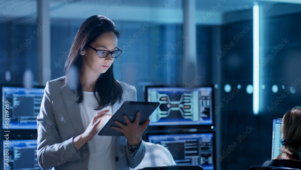 Fototapety, obrazy: Young Female Government Employee Wearing Glasses Uses Tablet in System Control Center. In the Background Her Coworkers are at Their Workspaces with many Displays Showing Valuable Data.