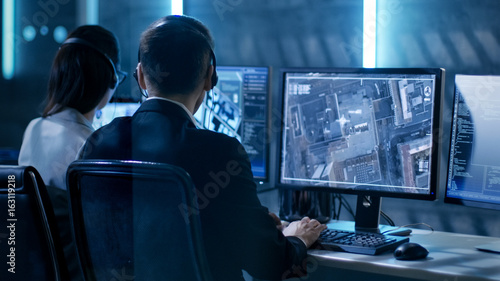 Valokuva  Government Agent is Tracking Fugitive with Her Computer in Big Monitoring Room Full of Computers with Animated Screens