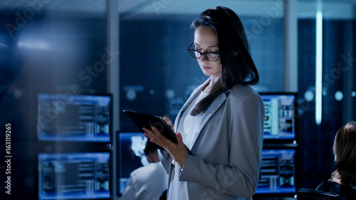 Photo  Young Female Engineer Uses Tablet in System Control Center