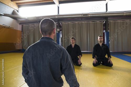 Back view of master in black kimono sitting in front of men