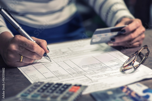 Valokuva  woman calculate how much cost or spending have with credit cards