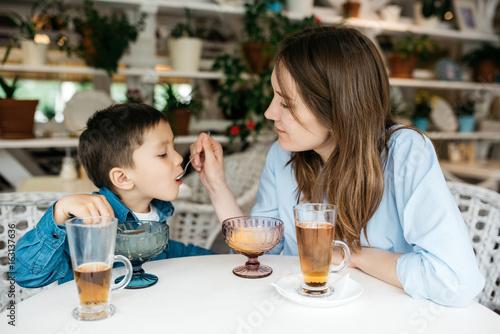 Plakat Mama karmi swojego synka lody w lekkiej kawiarni