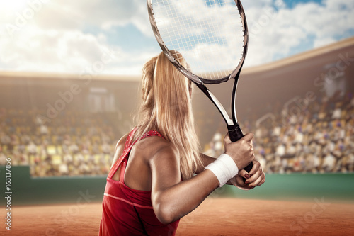 Fotografía  back view of a female tennis player on tennis court ready to hit a ball