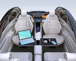 Rear view of autonomous car interior. Front seats turned around and laptop PC, smartphone and wireless headphone on folding table. Mobile office concept. 3D rendering image.