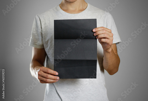 A man in a gray t-shirt holding blank clear black of the sheet. Closeup. Isolated